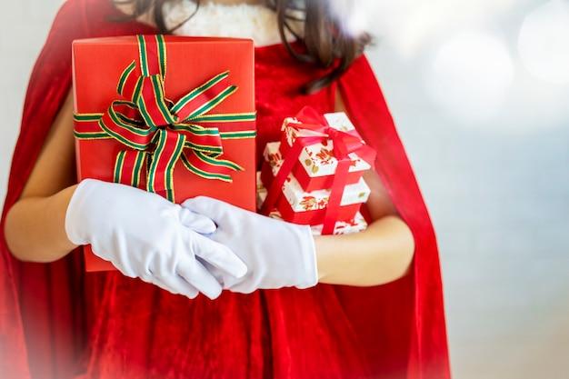 Concepto de fondo feliz navidad primer plano de la joven santaclaus en ropa roja con gif