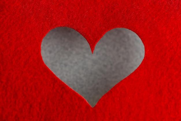 Concepto de fondo de fieltro para el diseño para el día de san valentín. corazón decorativo de fieltro rojo. vista desde arriba