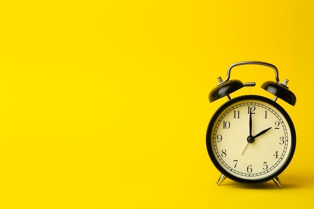 Concepto de fondo de tiempo. reloj despertador clásico vintage sobre fondo amarillo vacío. concepto de gestión del tiempo