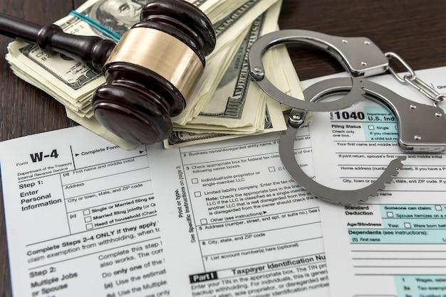 Concepto de formulario de impuestos nosotros dinero con esposas martillo acostado sobre impuestos federales