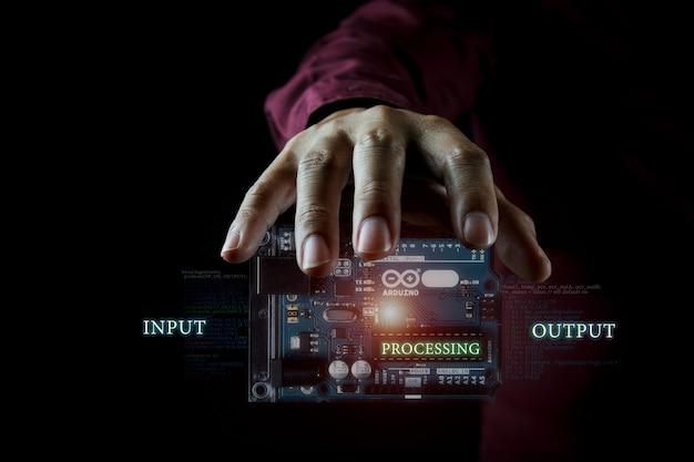 Concepto de foto del controlador arduino en el fondo oscuro y detalles infográficos