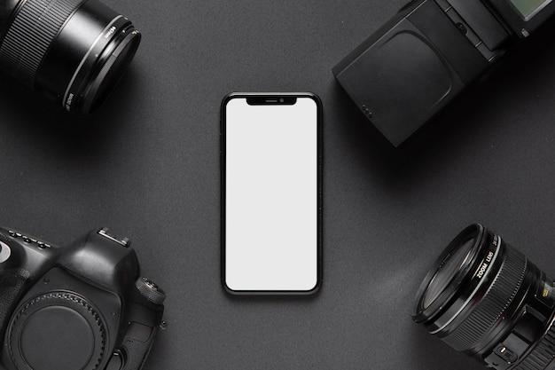 Concepto de fotografía con accesorios de cámara y teléfono inteligente en el medio