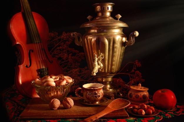 Concepto de fotografía de arte bodegón con samovar antiguo y violín aislado en un fondo negro