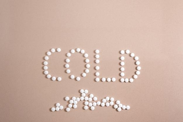 Concepto frío, palabra escrita con pastillas blancas redondas sobre fondo gris