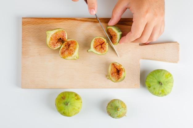 Concepto de frutas en plano. manos cortando higos sobre tabla de madera.