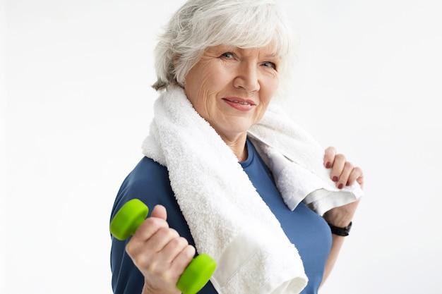 Concepto de fuerza, energía, bienestar y estilo de vida activo y saludable. elegante mujer senior atlética con cuerpo en forma y cabello gris retorciéndose en el gimnasio con mancuernas, vistiendo una toalla blanca alrededor de su cuello