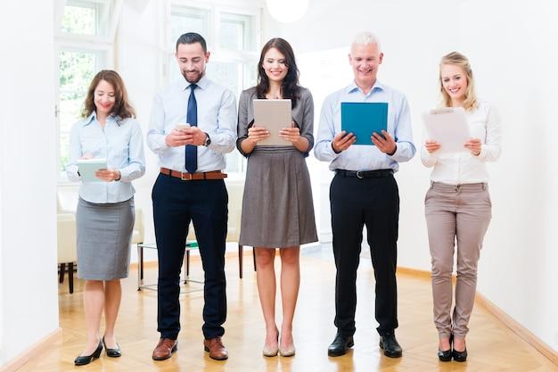 Concepto - gente de negocios en la oficina de pie en fila con teléfono, tableta y archivo