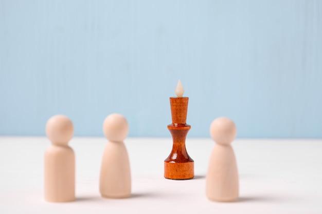Concepto de gestión de equipo. la figura del rey de madera sobre un fondo azul mira las figuras.