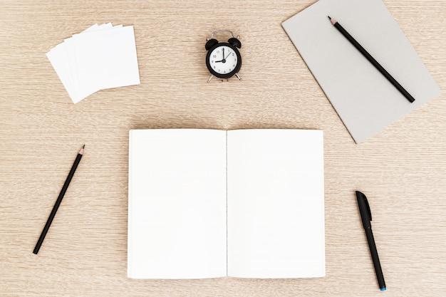 Concepto de gestión del espacio de trabajo y el tiempo. comienzo de la jornada laboral de autónomos. trabajar desde casa en cuarentena. cuaderno y monitoreo del tiempo, nueve de la mañana.