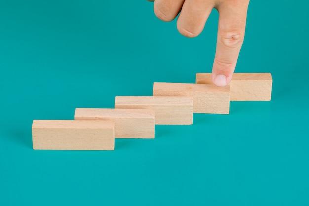 Concepto de gestión de negocios y riesgos en la vista de ángulo alto de la mesa turquesa. dedo que muestra el bloque de madera.