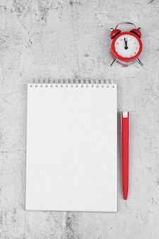Concepto de gestión del tiempo. lista de tareas: despertador rojo, lápiz y cuaderno