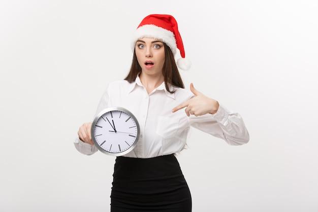 Concepto de gestión del tiempo - mujer de negocios joven con sombrero de santa sosteniendo y apuntando un reloj aislado sobre una pared blanca.