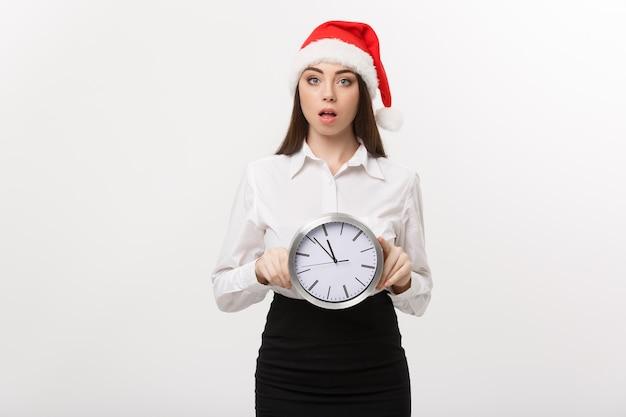 Concepto de gestión del tiempo - mujer de negocios joven con sombrero de santa sosteniendo un reloj aislado sobre una pared blanca.