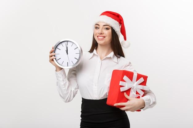 Concepto de gestión del tiempo - mujer de negocios joven con sombrero de santa sosteniendo un reloj y presente aislado sobre una pared blanca.