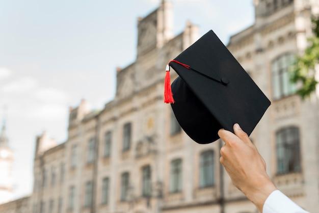 Concepto de graduación con estudiantes sujetando gorro
