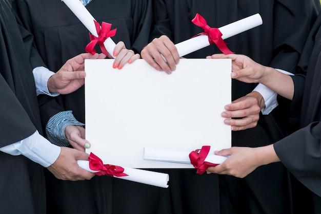 Concepto de graduación con estudiantes sujetando plantilla de certificado en blanco