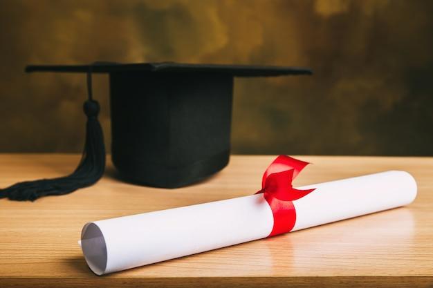 Concepto de graduación. gorro de graduación, sombrero con papel de grado en la mesa de madera.