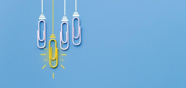 Concepto de grandes ideas con clip clip pensando creatividad bombilla sobre fondo azul.