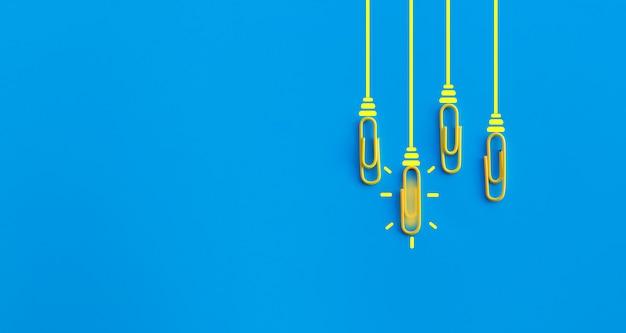 Concepto de grandes ideas con clip, pensamiento, creatividad, bombilla sobre fondo azul, nuevo concepto de ideas.