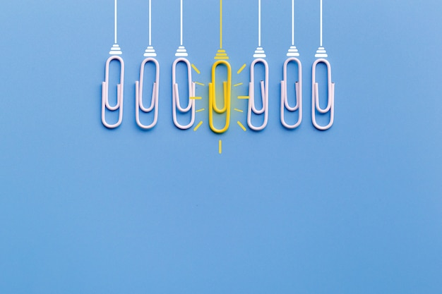 Concepto de grandes ideas con clip, pensamiento, creatividad, bombilla sobre fondo azul.