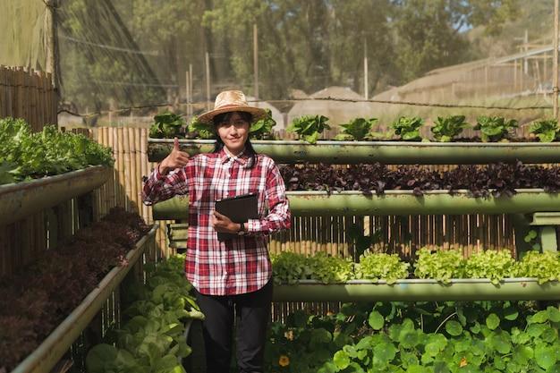 Concepto de granjero inteligente y productos vegetales; jardinero de sexo femenino que controla las plantas recién cultivadas en la granja con tableta y usa la aplicación para apoyar la granja inteligente