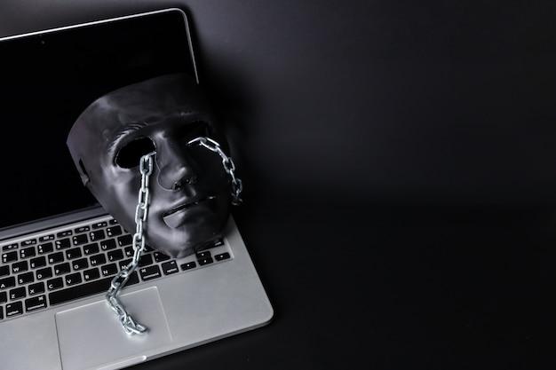 Concepto de hackers y delitos cibernéticos, máscara negra con cadena en computadora nueva sobre fondo negro