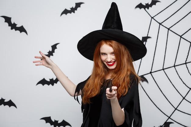 Concepto de halloween - bella bruja jugando con varita mágica en la pared gris.