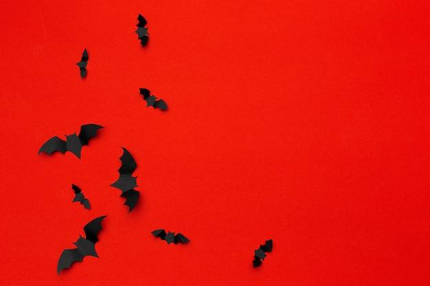 Concepto de halloween y decoración - murciélagos de papel volando sobre fondo rojo