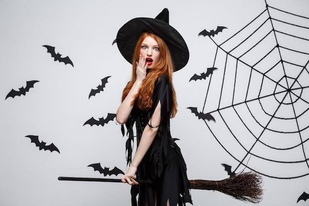 Concepto de halloween feliz bruja elegante disfruta jugando con escoba fiesta de halloween sobre pared gris