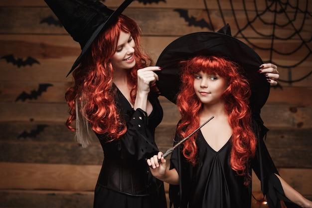 Concepto de halloween hermosa madre caucásica se viste para su hija en disfraces de bruja y largo c ...