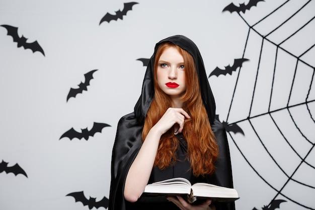 Concepto de halloween - hermoso hechizo de fundición de sacerdote oscuro con libro mágico en la pared gris.