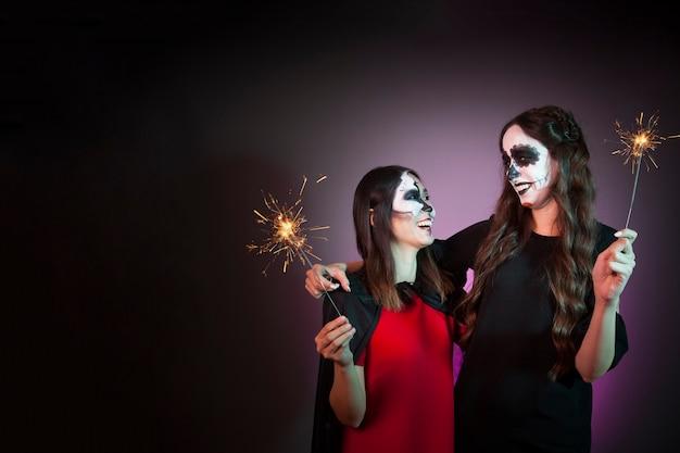 Concepto de halloween con mujeres sujetando bengalas