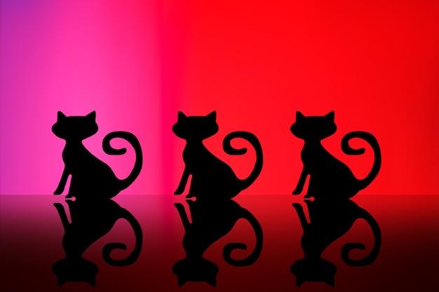 Concepto de halloween. silueta de gatos negros sobre un fondo rojo.