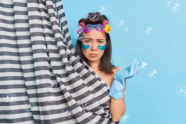 Concepto de higiene de la belleza de las mujeres de cuidado de la piel. mujer asiática morena insatisfecha frunce el ceño aplica parches de colágeno rizadores de pelo lleva guantes de goma posa detrás de la cortina de la ducha