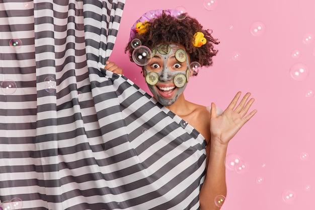Concepto de higiene y cuidado de la piel. la mujer afroamericana positiva levanta la palma se siente llena de alegría aplica la mascarilla facial de arcilla con rodajas de pepino disfruta de la ducha en el baño y de una piel impecable