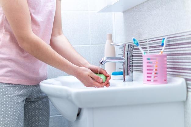 Concepto de higiene. lavarse las manos con jabón debajo del grifo con agua en el baño.