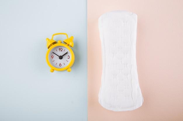 Concepto de higiene de la mujer de menstruación. almohadilla menstrual plana mínima y reloj despertador amarillo sobre un fondo rosa azul.