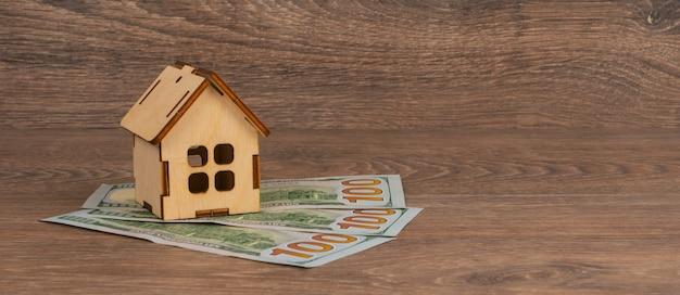 Concepto de hipoteca de la casa con modelo de casa de madera y billetes de 100 dólares