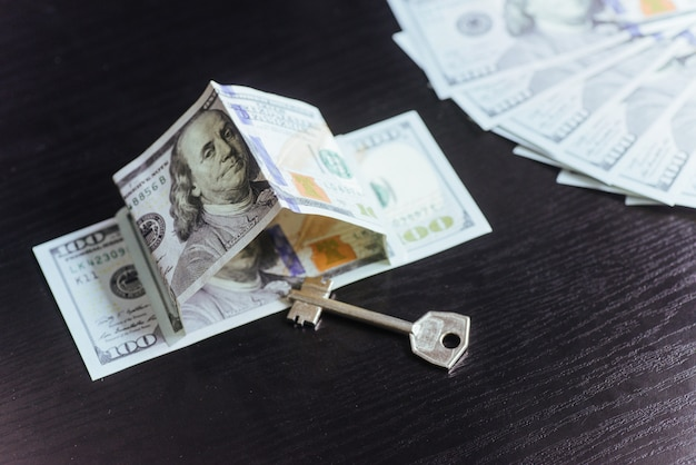 Concepto de hipoteca, inversión, bienes raíces y propiedad. dinero en dólares y llaves de la casa