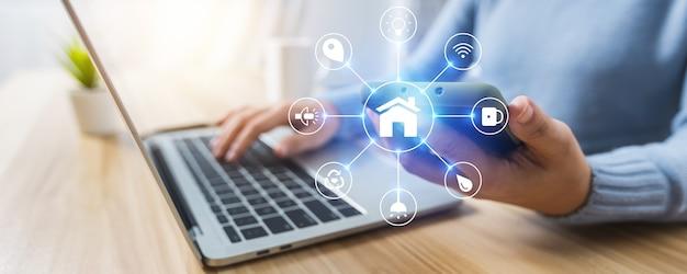 Concepto de hogar y tecnología inteligente, cerca de la mano de la mujer que sostiene el teléfono y se usa para controlar el móvil multimedia electrónico de bienes raíces Foto Premium
