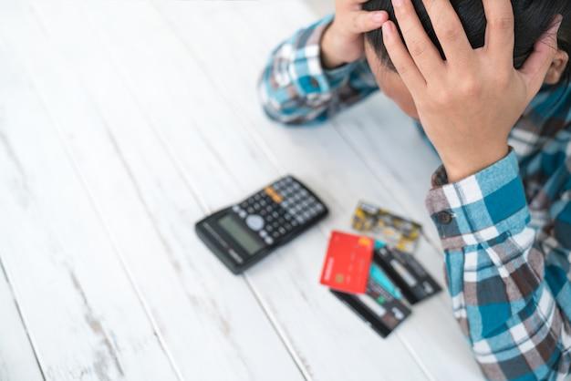 Concepto de el hombre está estresado con deuda debido al uso de tarjeta de crédito