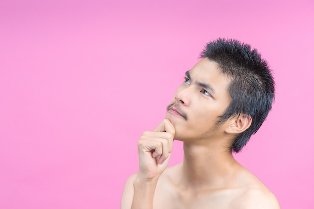 El concepto de un hombre joven sin una camisa que muestra gestos y rosa.