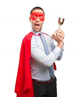 Concepto de un hombre de negocios super ganador con una taza de oro