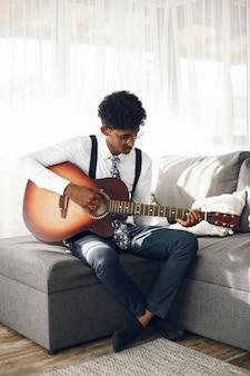 Concepto de hoobies. joven indio en medias sentado en la sala de estar. músico tocando la guitarra.