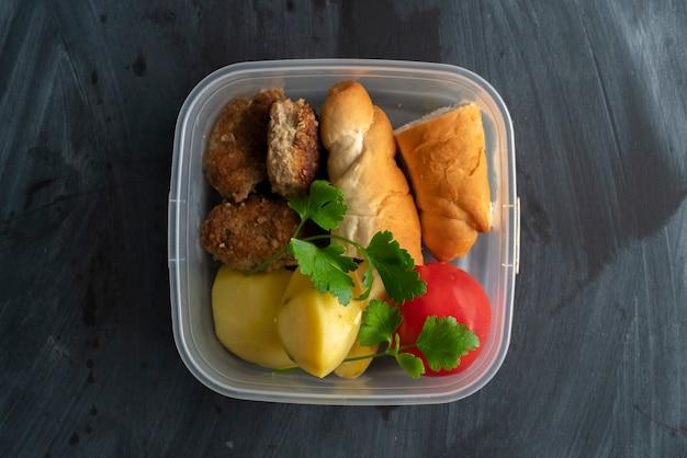 Un concepto de la hora del almuerzo, comiendo del recipiente de plástico con carne y papas en las mesas.