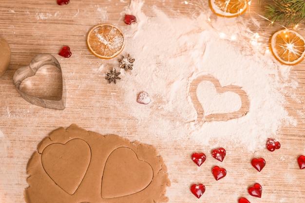 Concepto de horneado del día de san valentín con cortadores en forma de corazón y huevos en una mesa de madera oscura con copyspace