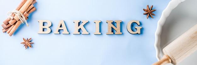 Concepto de horneado con fuente de horno blanca, rodillo, especias para hornear, sobre un fondo azul claro, banner de espacio de copia de vista superior