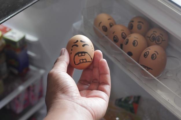 Concepto de huevo de gallina expresión de llanto cuando alguien lo saca de la nevera