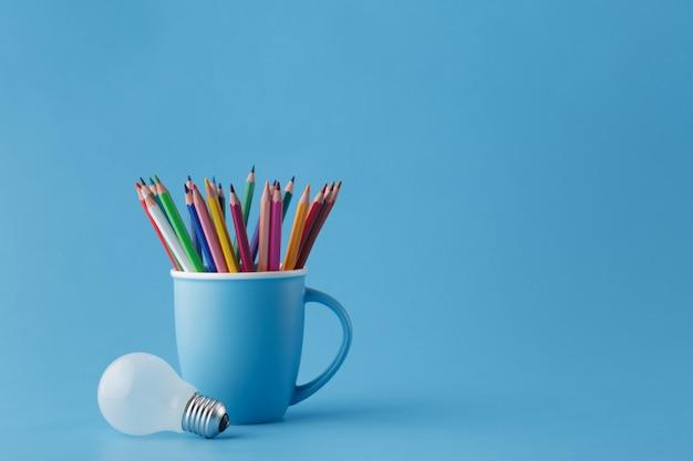 Concepto de idea creativa de arte, lápices en taza y bombilla