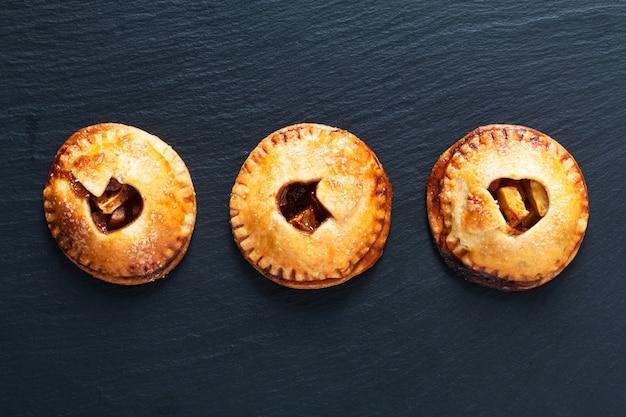 Concepto de idea de san valentín de alimentos pastel de mano de canela de manzana casera recién horneado en negro